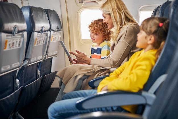 Vrouw in een vliegtuig toont een tablet aan een jongen