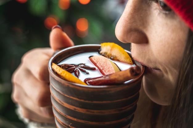 Vrouw in een warme trui drinkt aromatische hete glühwein