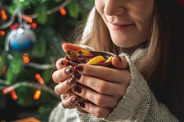 Vrouw in een warme trui houdt een kopje aromatische hete glühwein vast