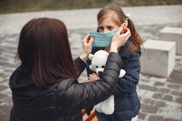Vrouw in een wegwerpmasker leert haar kind om een gasmasker te dragen