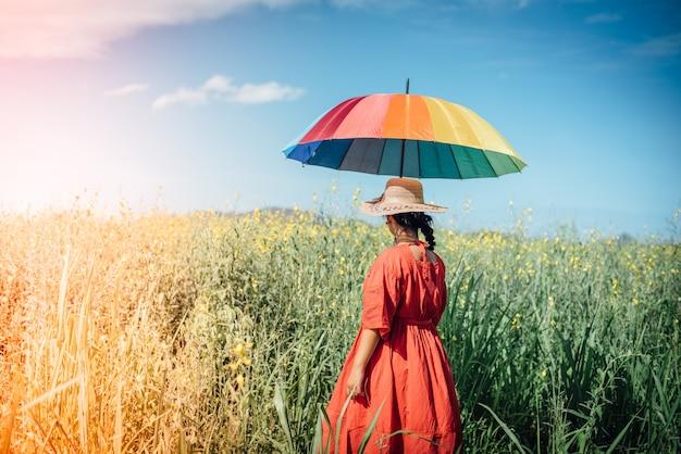 Vrouw in een weide met een paraplu