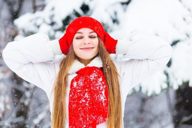 Vrouw in een winterjas en een rode hoed met een sjaal tegen de achtergrond van bomen bedekt met sneeuw