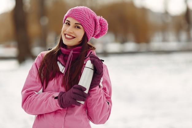 Vrouw in een winterpark. dame in roze sportpak. meisje met een thermoskan.