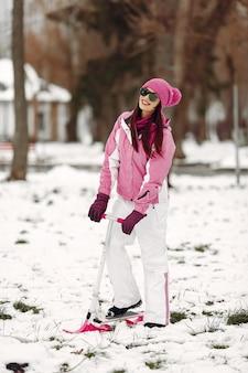 Vrouw in een winterpark. dame in roze sportpak. vrouw met sneeuwscooter.