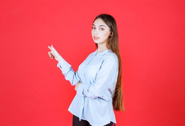 Vrouw in een wit overhemd dat op de rode muur staat en naar de achterkant wijst.