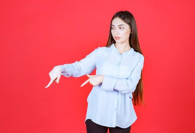 Vrouw in een wit overhemd dat op de rode muur staat en naar links wijst.