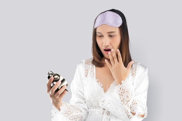 Vrouw in een wit satijnen nachthemd en in een kanten gewaad die laat in de ochtend wakker wordt en een wekker vasthoudt.