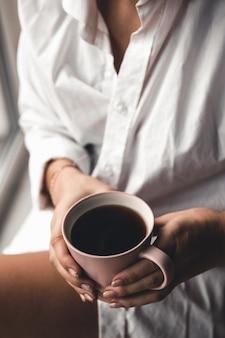 Vrouw in een wit t-shirt houdt 's ochtends koffie in een roze keramische beker. manicure. vooraanzicht