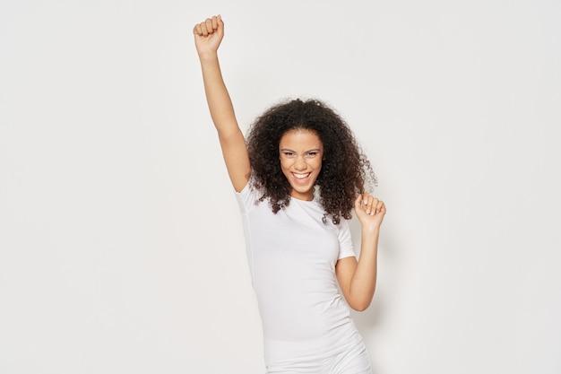 Vrouw in een wit t-shirt met krullend haar stak haar hand op tegen een lichte achtergrond