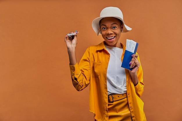 Vrouw in een witte hoed in geel overhemd glimlacht naar de camera met een speelgoedvliegtuig met een paspoort met kaartjes in handen. reis concept
