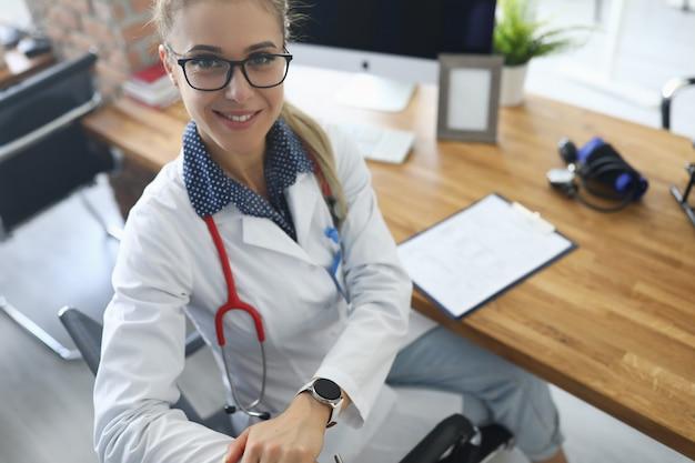 Vrouw in een witte jas zitten aan een tafel in een kliniek