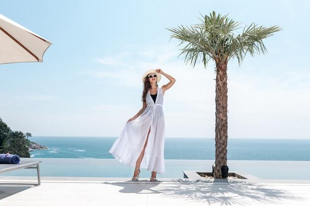 Vrouw in een witte jurk en hoed poseren in de buurt van een palmboom