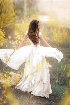 Vrouw in een witte jurk in volle groei in een tuin met bomen met gele bloemen