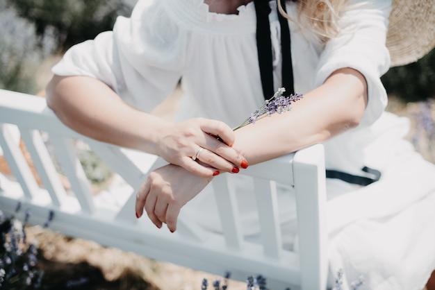 Vrouw in een witte jurk op een bankje onder lavendel