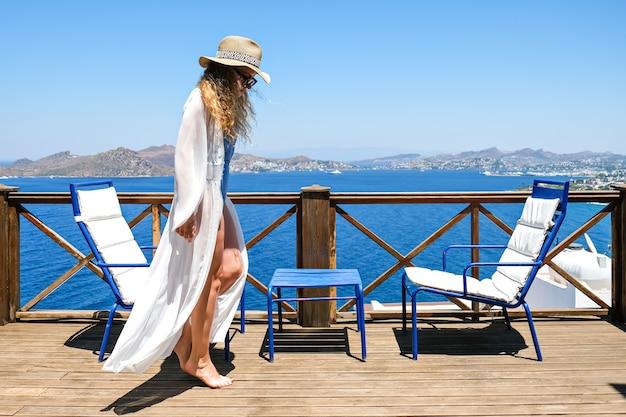 Vrouw in een witte jurk op het terras