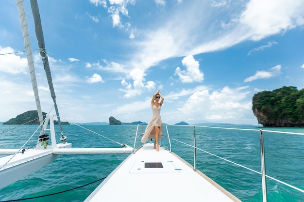 Vrouw in een witte rok die zich op een jacht bevindt