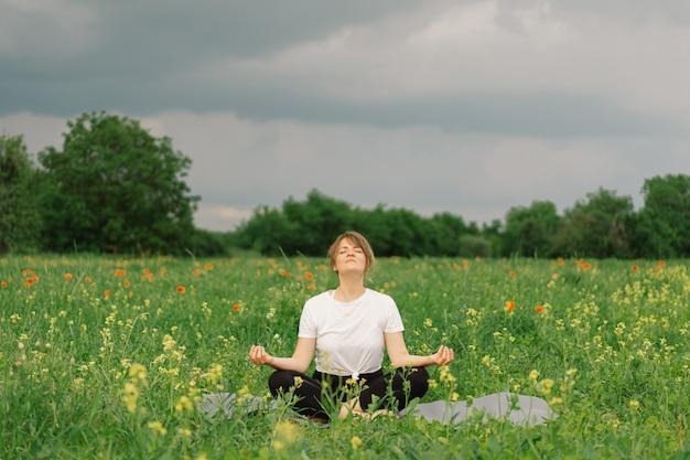 Vrouw in een witte t-shirt en legging die yoga doet in een prachtig veld op een sportmat-levensstijl