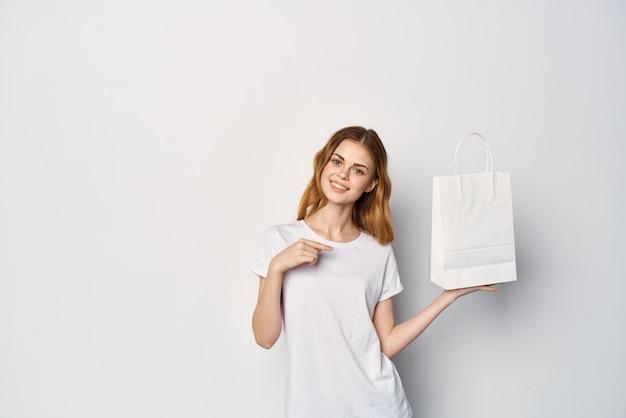 Vrouw in een witte t-shirt met een pakket in haar handen gebaren met haar handen mockup