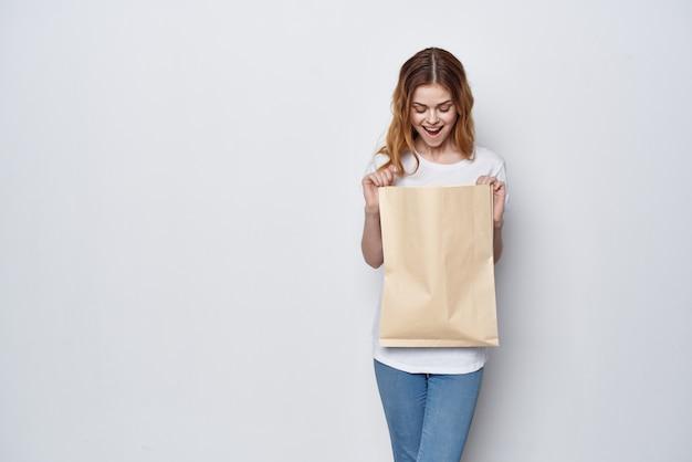 Vrouw in een witte t-shirt met een pakket in haar handen winkelen