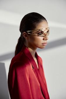 Vrouw in een zijden jasje met decoratie op haar gezicht zijaanzicht op een lichte achtergrond. hoge kwaliteit foto