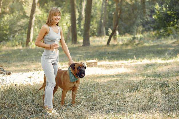 Vrouw in een zomer bos spelen met hond