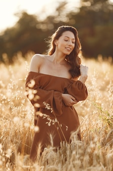 Vrouw in een zomer-veld. brunette in een bruine trui.