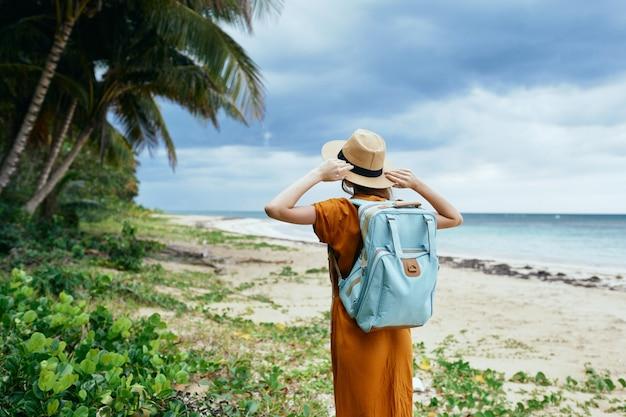 Vrouw in een zomerjurk en hoed op het eiland bij de bomen en de zeerugzak op de achtergrond
