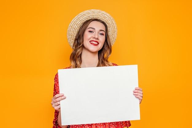 Vrouw in een zomerjurk heeft een lege a4 poster van papier en glimlacht geïsoleerd op oranje achtergrond