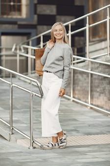 Vrouw in een zomerstad. dame met bruine zakken. vrouw in een grijze trui.
