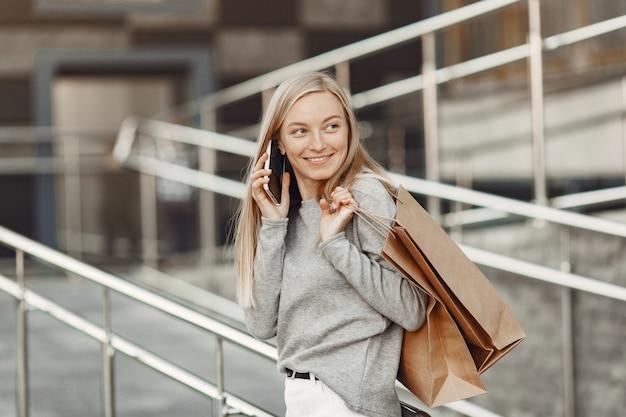Vrouw in een zomerstad. dame met mobiele telefoon. vrouw in een grijze trui.