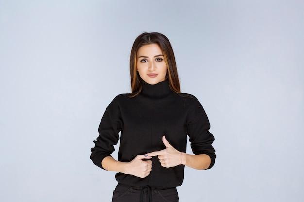 Vrouw in een zwart shirt dat naar links wijst en haar emoties toont.
