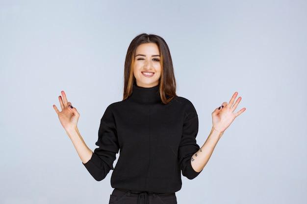 Vrouw in een zwart shirt met een teken van plezier.