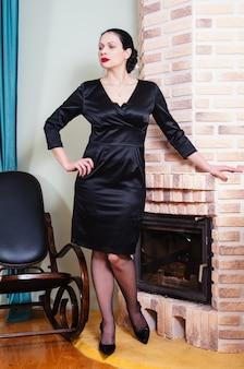 Vrouw in een zwarte avondjurk die bij de open haard staat