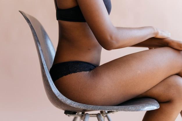 Vrouw in een zwarte beha zittend op een stoel