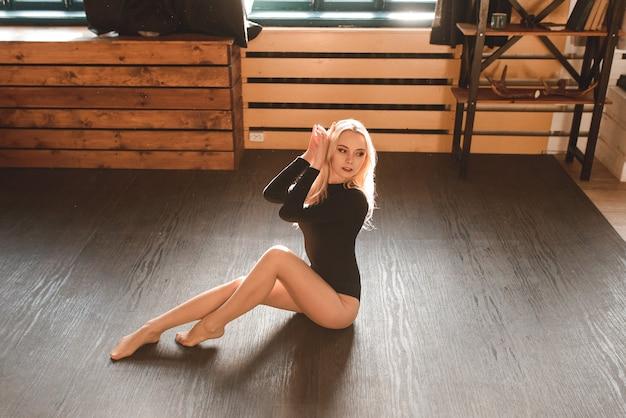 Vrouw in een zwarte bodysuit. sensuele prachtige jonge dame poseren in de studio