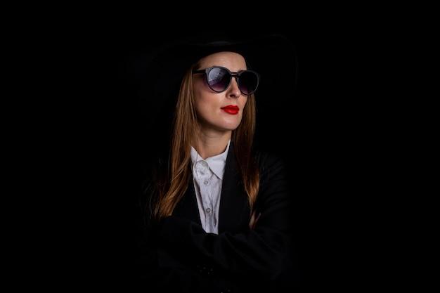 Vrouw in een zwarte hoed, bril en een jas op een zwarte.