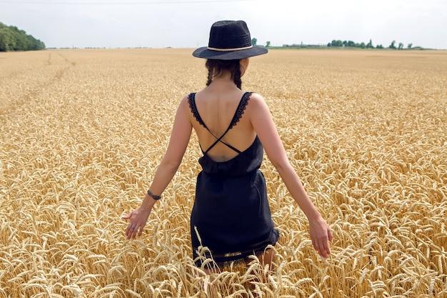 Vrouw in een zwarte jurk en een hoed staat in een geel veld