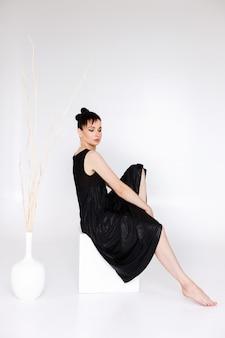 Vrouw in een zwarte jurk op een witte achtergrond