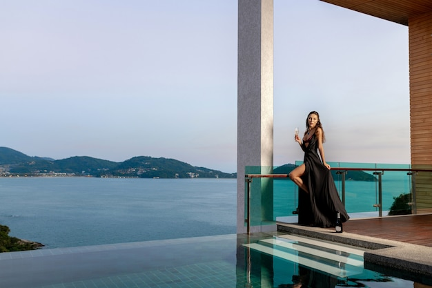 Vrouw in een zwarte lange jurk staat met een glas champagne in de buurt van het zwembad