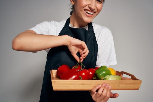 Vrouw in een zwarte schort een dienblad met groenten gezond voedsel huishoudelijk werk