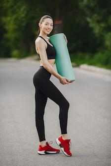 Vrouw in een zwarte sportkleding die zich in een bos bevindt