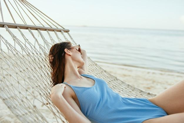 Vrouw in een zwembroek in een hangmat op een ruimte van de oceaan
