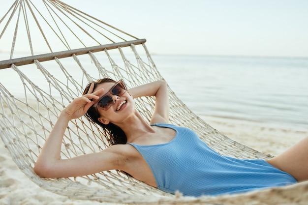Vrouw in een zwempak in een hangmat op het strand, uitzicht op zee