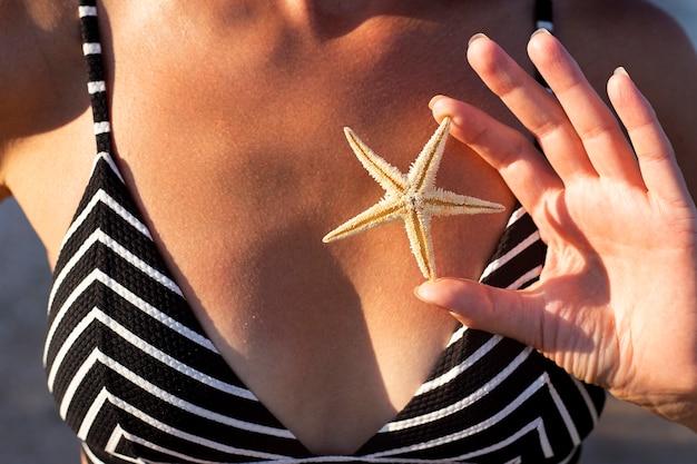 Vrouw in een zwempak tegen de achtergrond van een gebruind lichaam houdt een zeester vast. Premium Foto