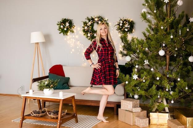 Vrouw in elegante jurk naast kerstboom