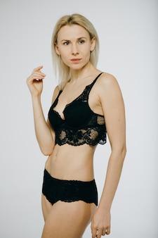 Vrouw in erotische zwarte lingerie die over wit wordt geïsoleerd. mooie schoonheid in zwart ondergoed.
