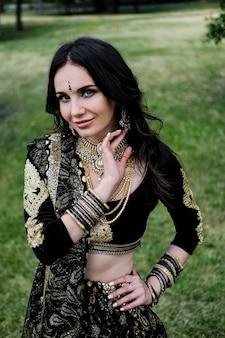 Vrouw in etnisch indisch kostuum met juwelen en traditionele make-up.