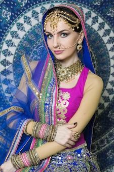 Vrouw in etnisch kostuum met juwelen en traditionele make-up