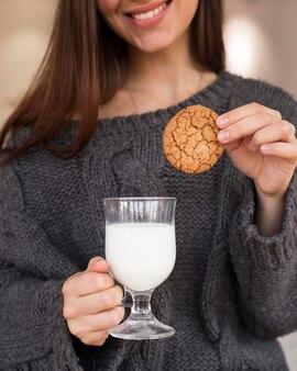 Vrouw in fauteuil met koekje en melk