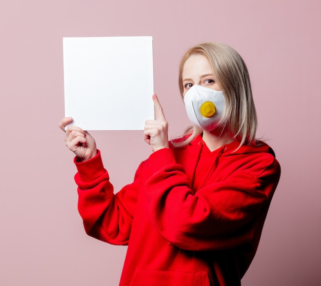 Vrouw in ffp2 anti-stof standaard gezichtsmasker houdt banner op roze achtergrond